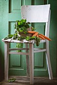 Fresh spinach and carrots on an old white wooden chair against a green wooden wall