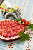 Strawberry cake with a jell topping on a table outside