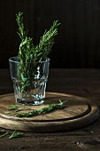Rosemary sprigs in a glass of water on a round wooden board