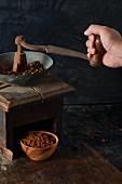 Kaffeebohnen werden mit antiker Holzkaffeemühle gemahlen