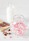 A bottle of milk, a bar of chocolate and candy canes in a sweetie jar