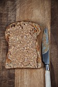Wholemeal toast with peanut butter spread on a chopping board with a knife