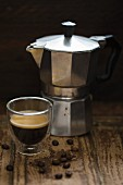 An espresso maker and a glass of espresso