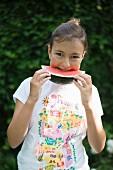 Mädchen isst Wassermelone im Garten