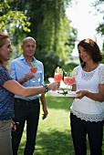 Drei Erwachsene mit Cocktail im Garten
