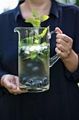Erfrischungsgetränk mit Blaubeeren und Kräutern in Glaskanne gehalten