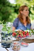 Erfrischungsgetränk mit Blaubeeren in Glaskanne und frische Erdbeeren in Glasschale auf Gartentisch