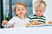Zwei Kleinkinder essen Spaghetti mit Tomatensauce
