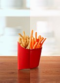 Half a packet of fries and half a cup of carrot crudites (photo collage)