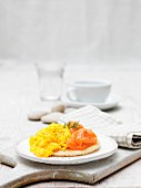Smoked salmon and scrambled eggs on blini garnished with dill