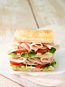 Wafer thin roast chicken with tomato and lettuce leaves