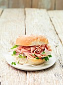 Wafer thin smoked ham on a roll with leafy vegetables