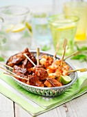 A mini grill selection featuring king prawns, chicken wings and pork in a vintage basket on a garden table