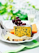 A selection of cheese with crackers and grapes on a garden table