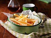 French fries in an enamel bowl on a tea towel with a bottle of vinegar