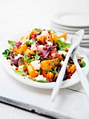 A salad with pumpkin, feta cheese, red onions, pomegranate seeds and mixed leaf salad