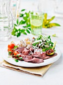 Roast beef with herb salad, tomatoes and potatoes