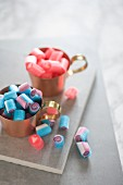 Blue and pink sweets in copper cups