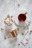 An arrangement of tea and grape sugar sweets in a copper cup