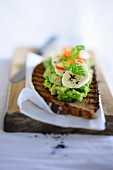 A slice of grilled bread topped with avocado cream and bananas