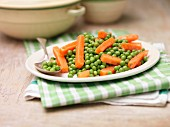 A plate of peas and carrots with mint and butter on a tea towel