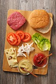 Ingredients for a cheeseburger on a chopping board