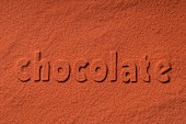 The word 'chocolate' written in cocoa powder