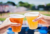 Hands raising a toast with beer in plastic cups