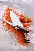 Two different kitchen knives and cherry tomatoes