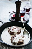 Beef fillet with a creamy sauce and pink peppercorns in a pan