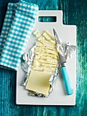 White chocolate in silver foil on a chopping board