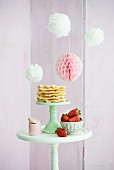 Pompons und Wabenball, Tisch mit Waffeln und Erdbeeren