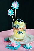 Ice cubes, blueberries and paper flowers on swizzle sticks in glass