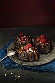 Mini chocolate cakes with chocolate glaze and raspberries