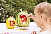 Melonenwürfel in ausgehöhlten Melonenschalen, Mädchen nimmt sich ein Stück mit Spiesschen