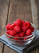 Fresh raspberries in a glass bowl on a wooden surface