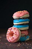 A stack of doughnuts with blue and pink icing and sugar sprinkles