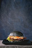 Homemade black burger with salmon, sprouts and lettuce