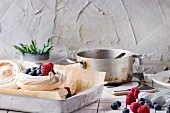 Meringue nests with berries for Pavlova on a kitchen table