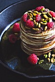 A stack of pancakes with chocolate cream, pistachio nuts and raspberries