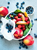Fresh fruit and spinach in a bowl with other fruit next to it