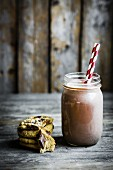 Chocolate milk in a jar with a straw with cookies next to it