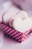 Pastel coloured heart-shaped biscuits in a paper box decorated with hearts