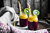 Two layer smoothies with straws in screw-top jars