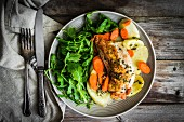 Chicken breast with potatoes and rocket salad on a rustic surface
