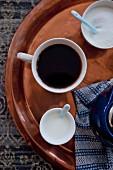 Eine Tasse Kaffee mit Milch und Zucker auf Kupfertablett (Aufsicht)