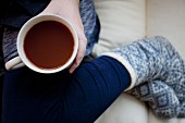 Frau mit Tasse Kaffee und Wintersocken auf Sofa sitzend