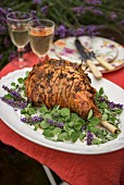 Leg of lamb with lavender and garlic on a table outside