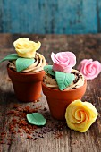Muffins with caramel frosting and fondant roses in flower pots