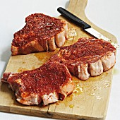 Marinated pork chops on a wooden chopping board